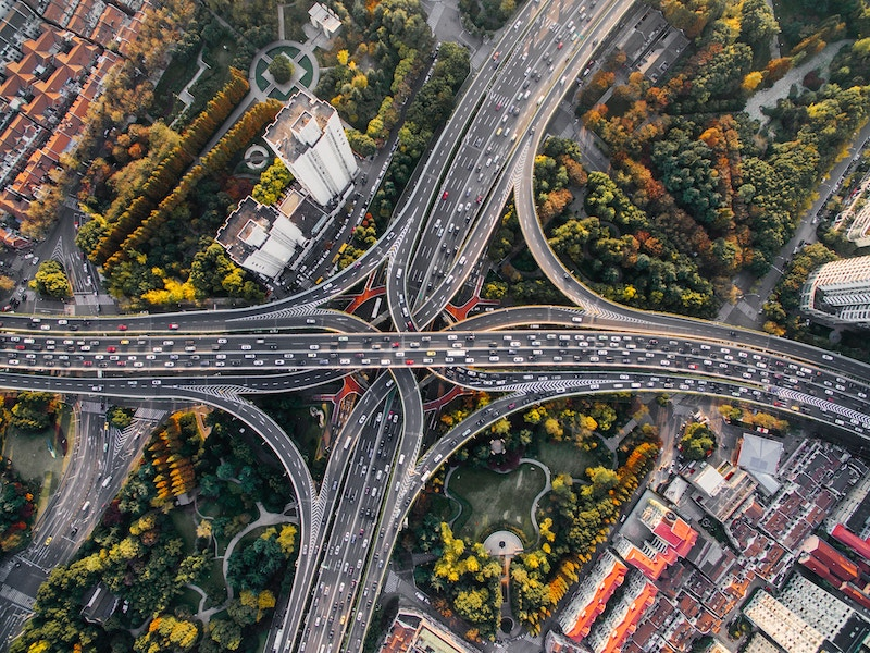 An aerial view of an intricate freeway system during the day with heavy traffic
