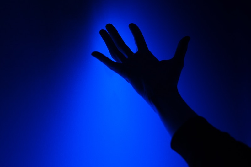 Outstretched hand with bright blue neon background